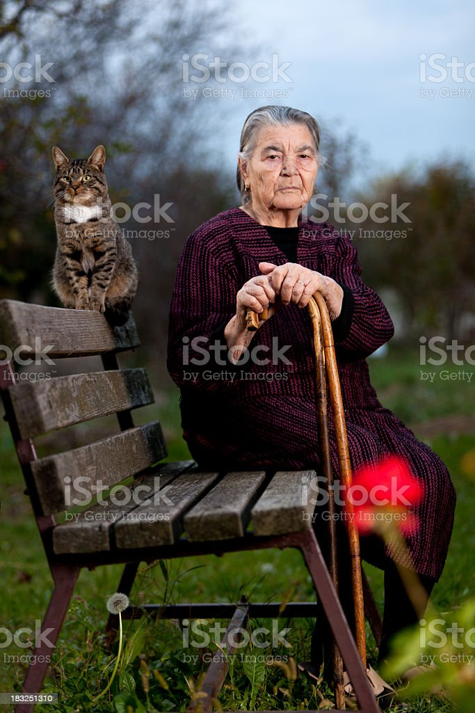 Portrait of senior woman and cat sitting on bench outdoors royalty-free stock photo