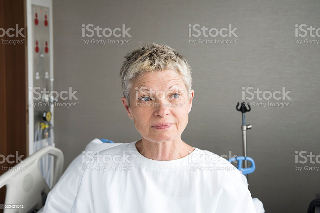 Portrait of senior woman in hospital wearing gown stock photo