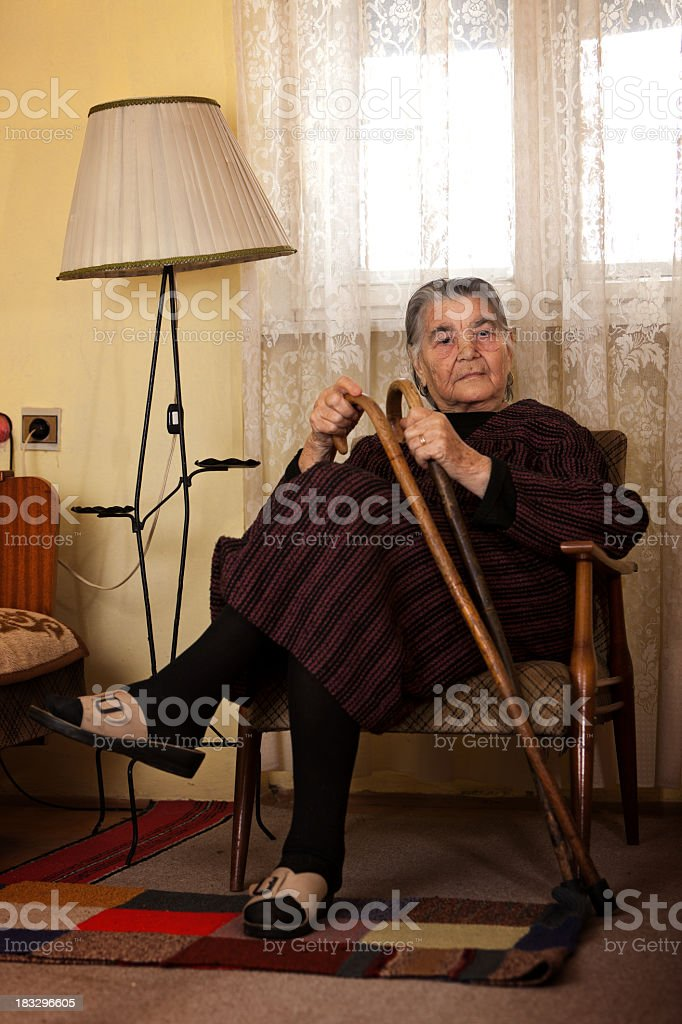 Portrait of senior woman with walking sticks in domestic room royalty-free stock photo