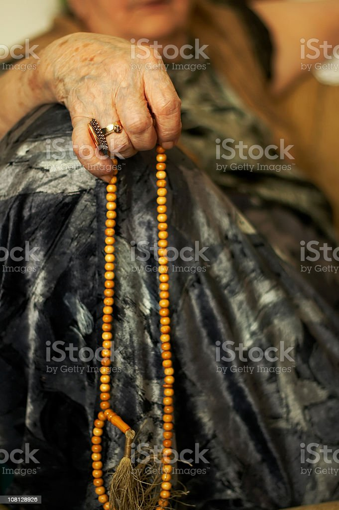 Portrait of Senior Woman's Hands Holding Prayer Beads royalty-free stock photo