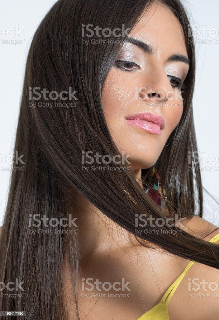 Portrait of sensual feminine woman holding straight brown hair lock stock photo