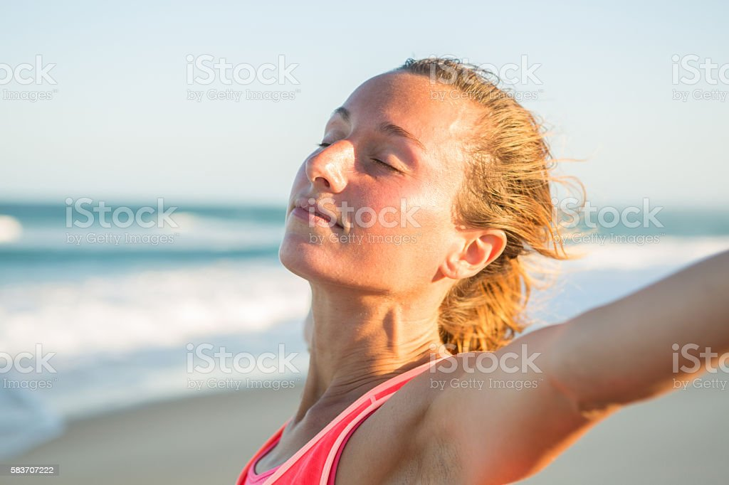 Portrait of serene woman on beach relaxing after training stock photo
