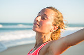 Portrait of serene woman on beach relaxing after training