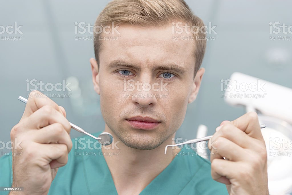 Portrait of serious dentist holding dental pick royalty-free stock photo