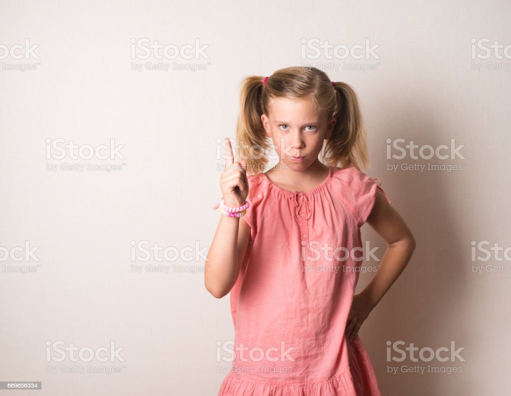 Portrait of serious, frowning, angry, grumpy girl pointing finger upwards, scolding someone. stock photo