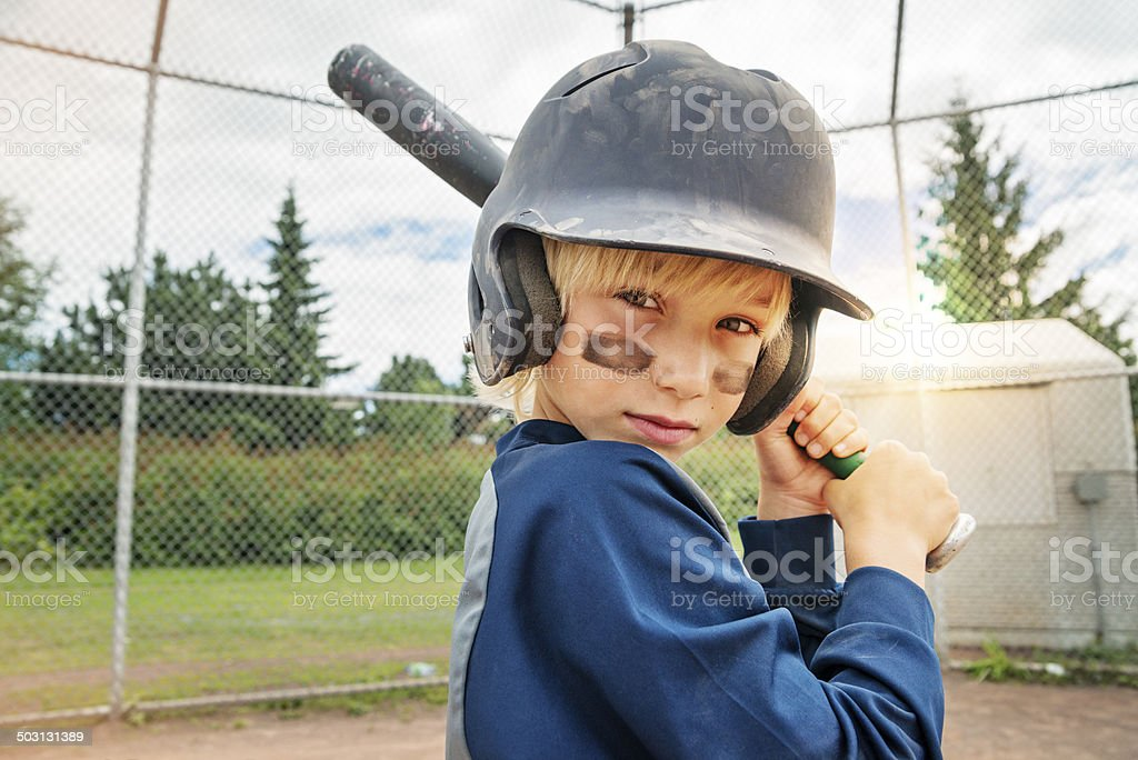 Portrait of serious little boy ready to play baseball. stock photo