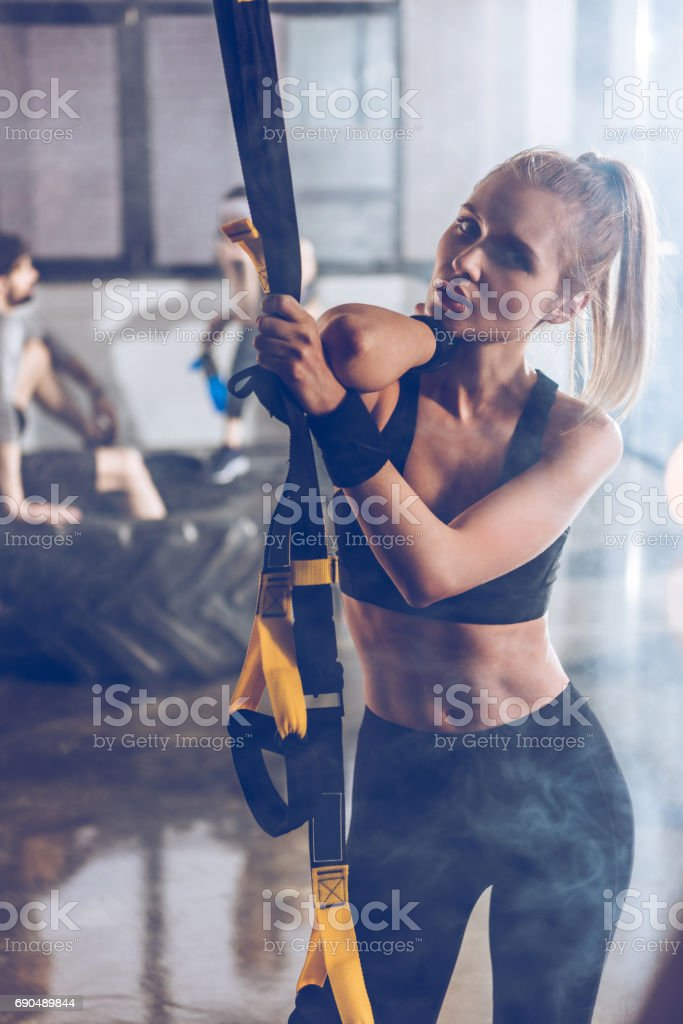 portrait of serious sportive woman holding trx gym equipment stock photo