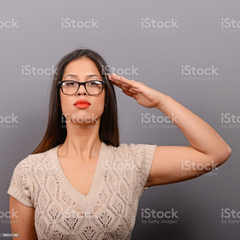 Portrait of serious woman saluting in casual clothes against gray background stock photo