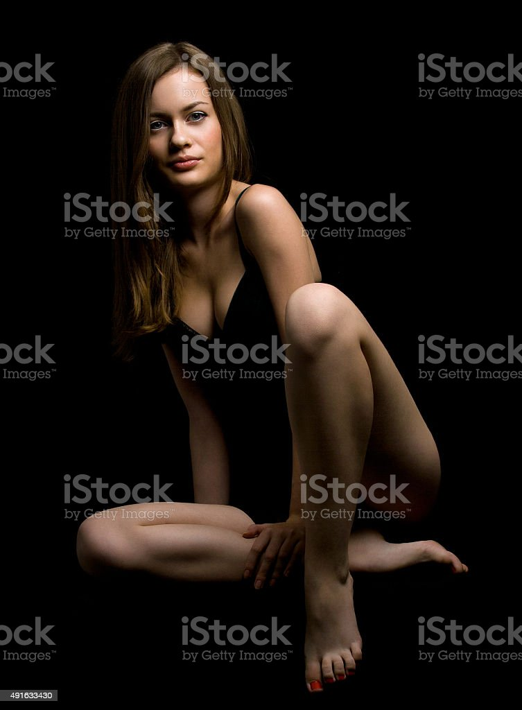 Portrait of sexy woman posing in black lingerie over black background stock photo