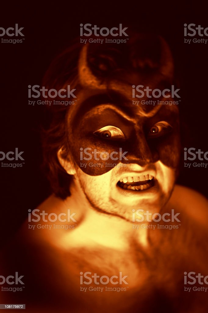 Portrait of Shirtless Man Wearing Devil Mask, Toned royalty-free stock photo