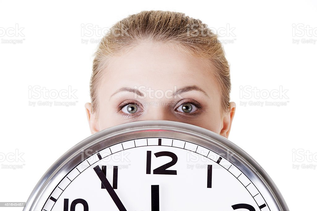 Portrait of shocked woman with clock. stock photo