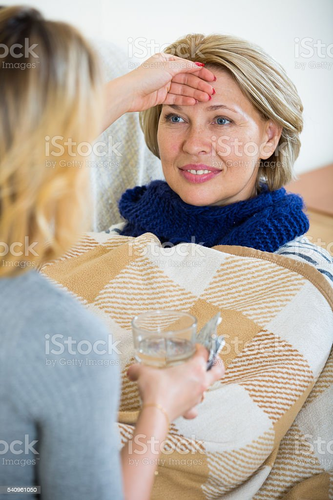 Portrait of sick female pensioner and her careful daughter stock photo
