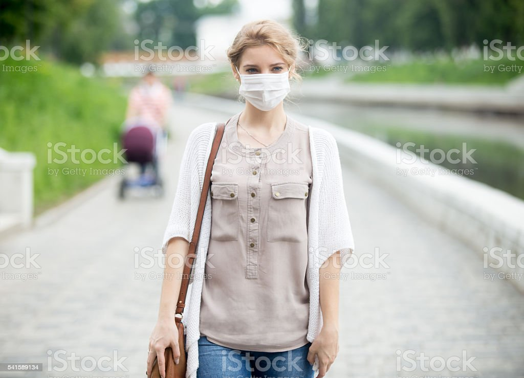 Portrait of sick woman wearing protective mask against infective stock photo