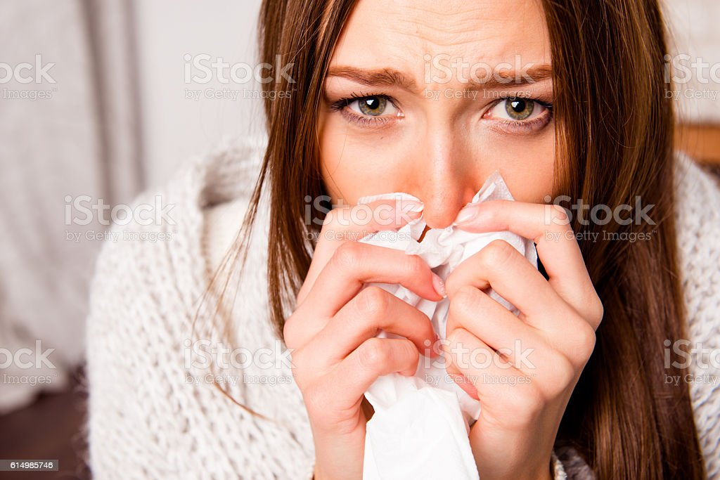 portrait of sick woman  with fever sneezing in tissue stock photo