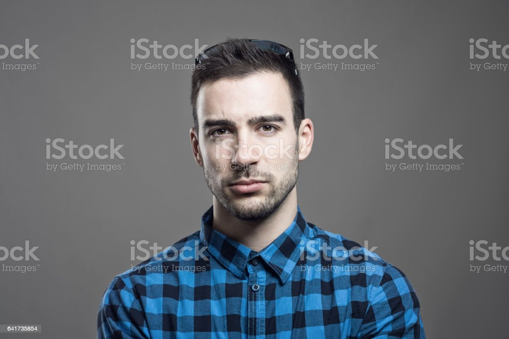 Portrait of skeptical young man frowning face looking at camera stock photo