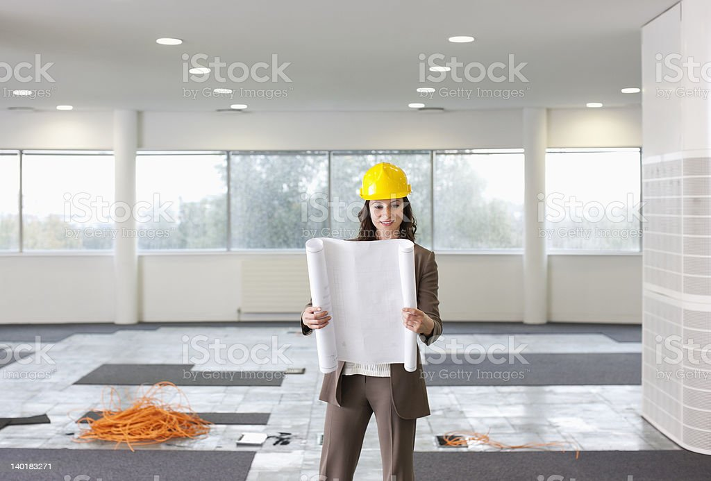Portrait of smiling architect holding blueprint in empty office stock photo