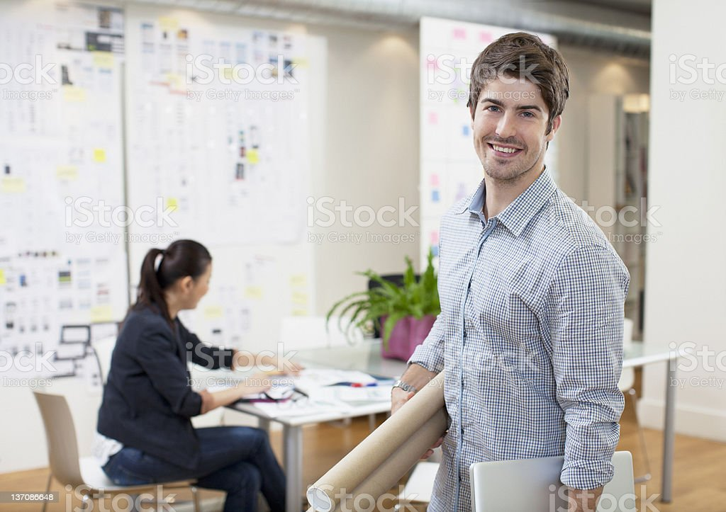 Portrait of smiling architect holding blueprint tubes in office royalty-free stock photo