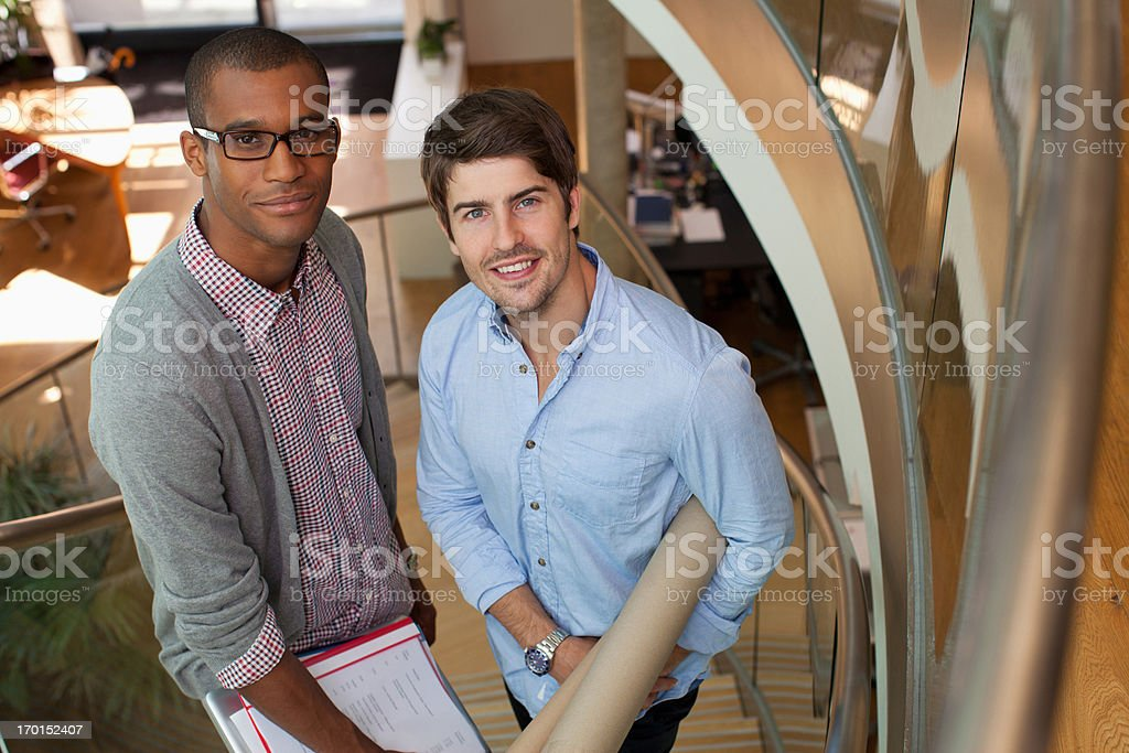 Portrait of smiling architects with blueprint tubes on stairs in office royalty-free stock photo