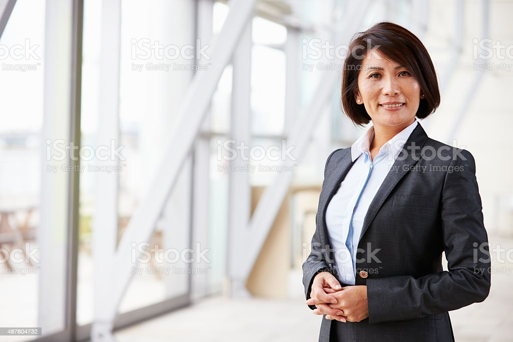 Portrait of smiling Asian businesswoman, standing stock photo
