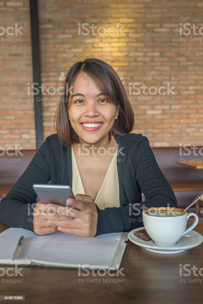 Portrait of smiling Asian office lady carrying smartphone stock photo