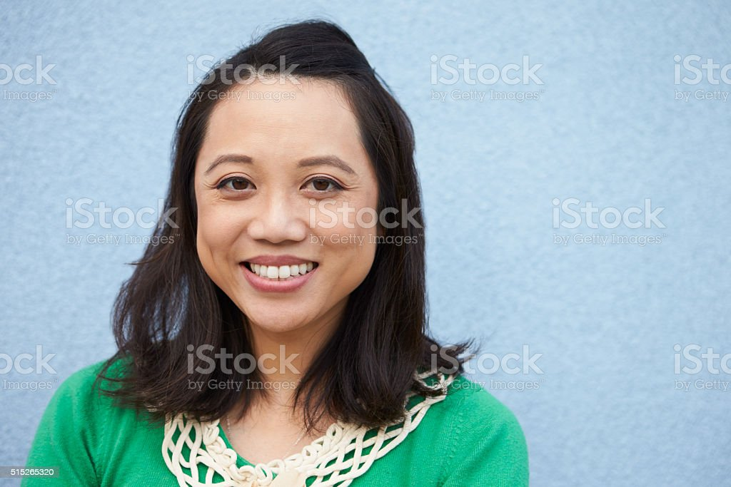 Portrait of smiling Asian woman against grey wall stock photo