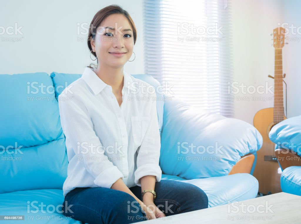 A portrait of smiling Asian woman sitting on sofa at living room stock photo