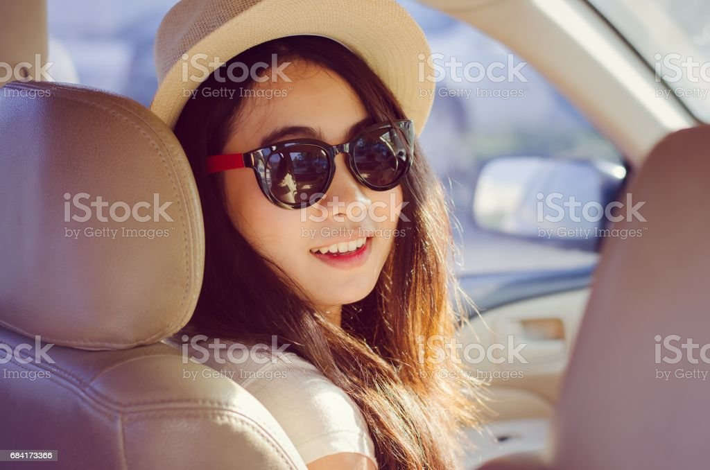 A portrait of smiling Asian woman with travel by car stock photo