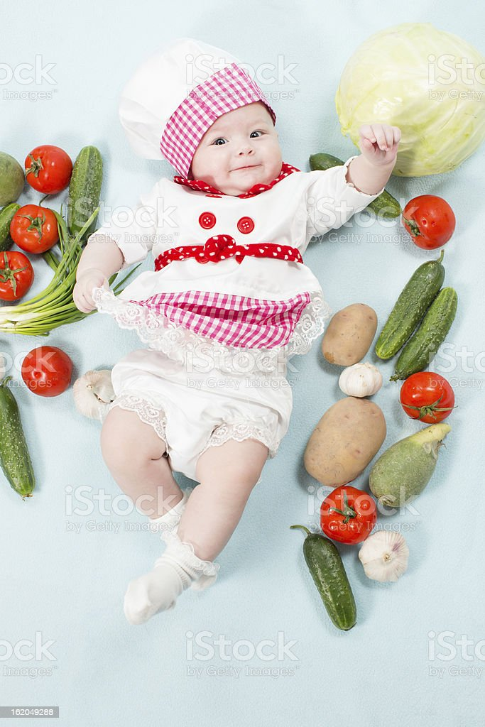 Portrait of smiling baby wearing chef hat by vegetables stock photo