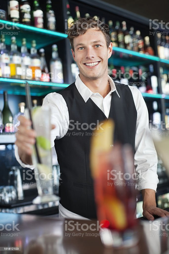 Portrait of smiling bartender holding cocktail royalty-free stock photo