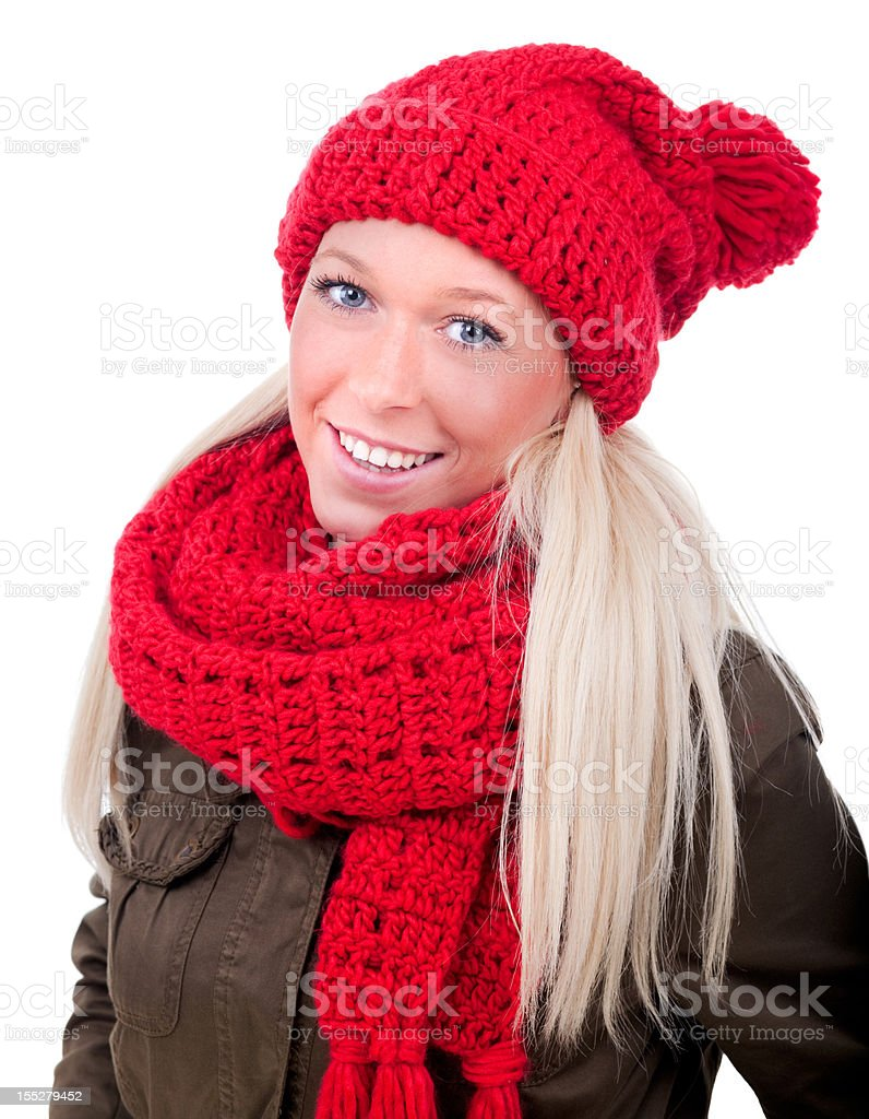 Portrait of smiling blond female with blue eyes wearing a red knitted beanie and scarf and a brown coat in front of white background royalty-free stock photo