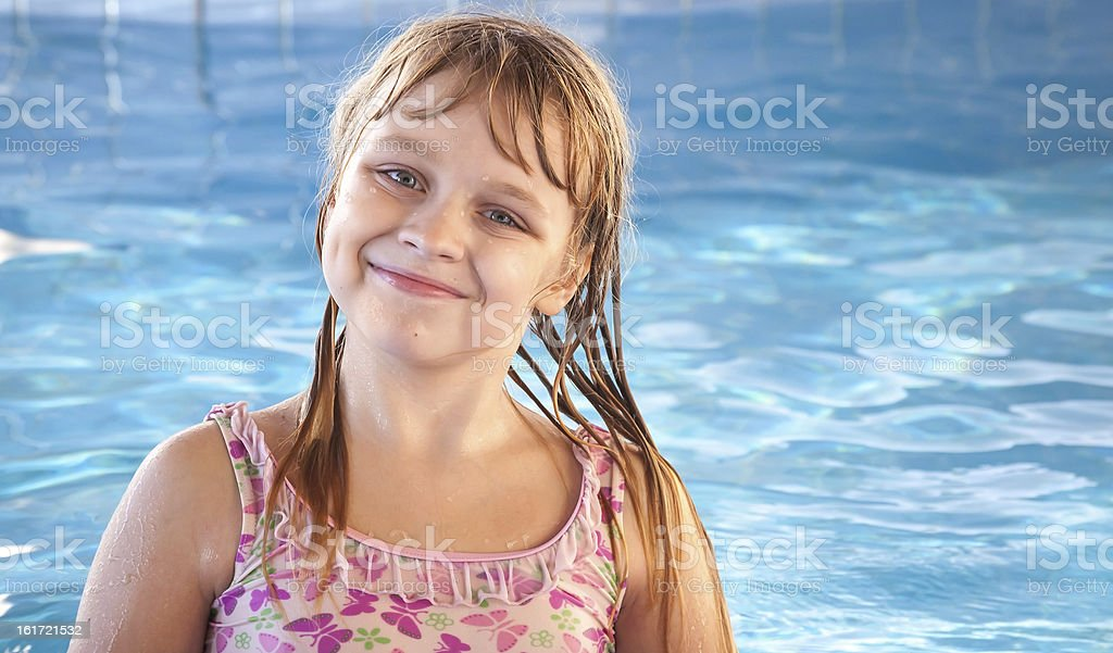 Portrait of smiling blond girl with bright blue pool water royalty-free stock photo