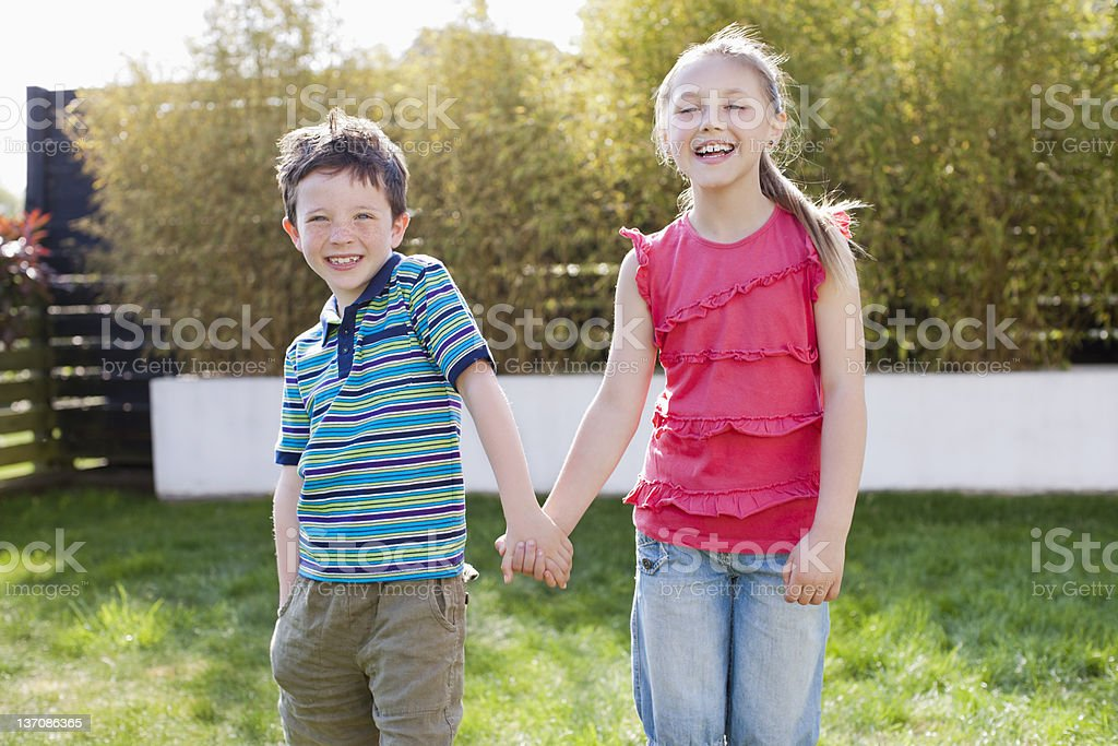Portrait of smiling boy and girl holding hands in backyard royalty-free stock photo