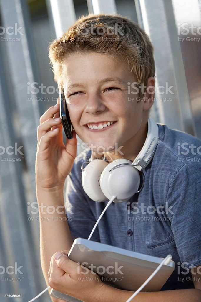 Portrait de garçon souriant talking sur téléphone intelligent. photo libre de droits
