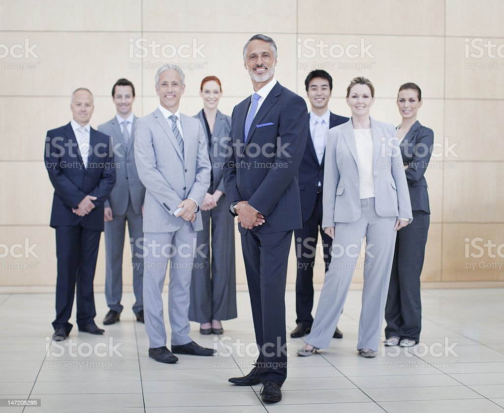 Portrait of smiling business people at bottom of escalator royalty-free stock photo