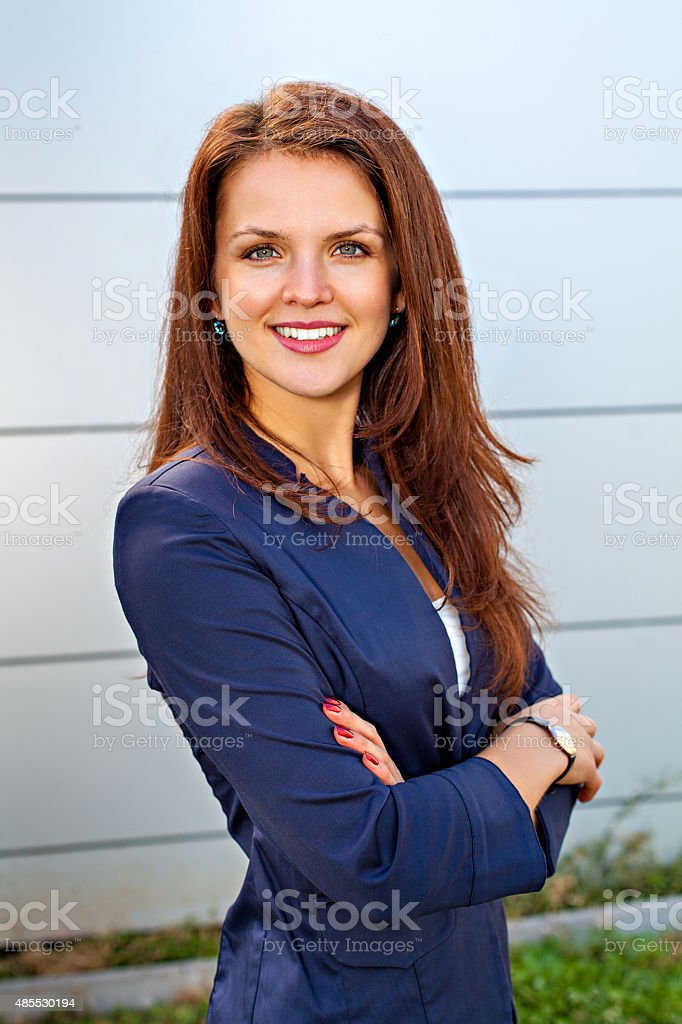 Portrait of smiling business woman with hands folded stock photo