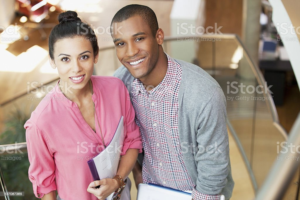 Portrait of smiling businessman and businesswoman on stairs in office royalty-free stock photo