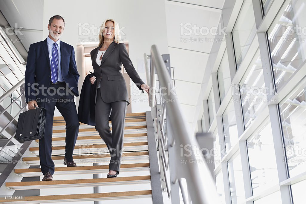 Portrait of smiling businessman and businesswoman on stairs stock photo