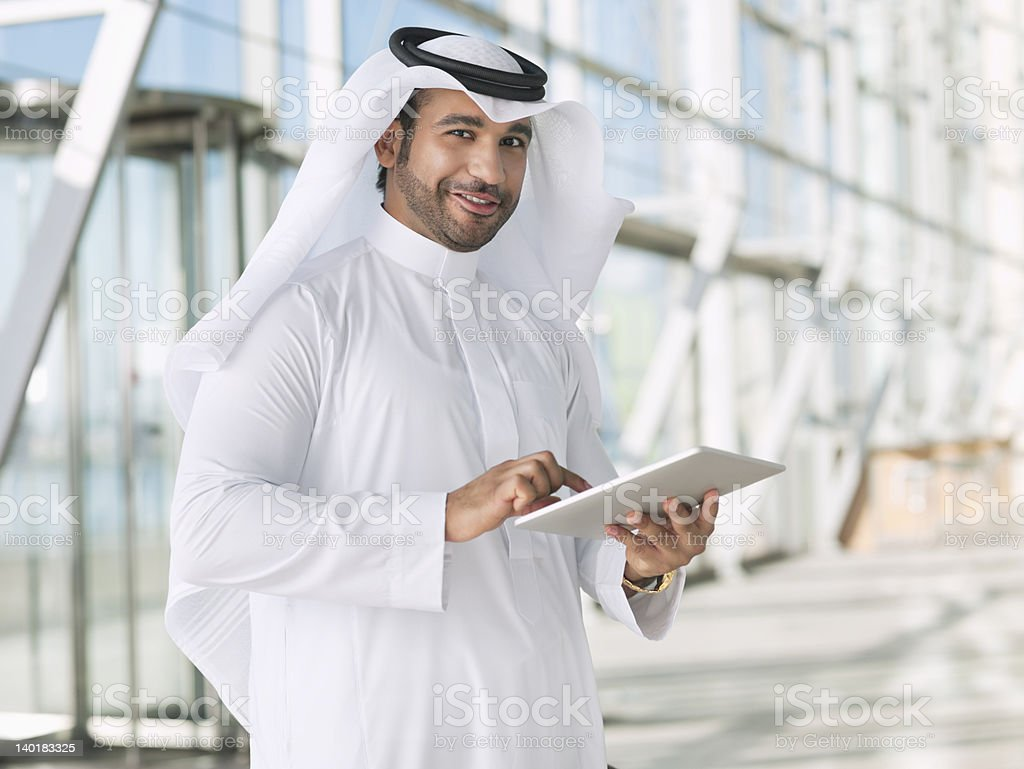 Portrait of smiling businessman in kaffiyeh using digital tablet stock photo