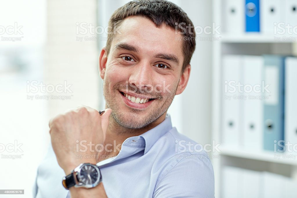 portrait of smiling businessman in office stock photo