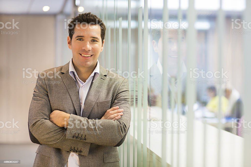 Portrait of smiling businessman standing in hall stock photo