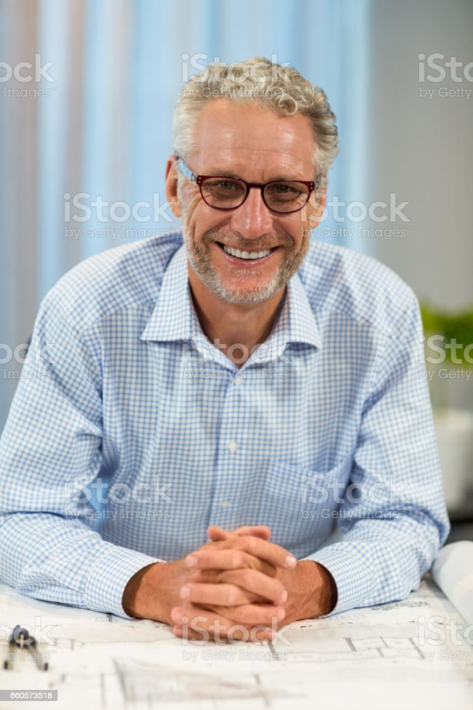 Portrait of smiling businessman with blueprint on desk stock photo