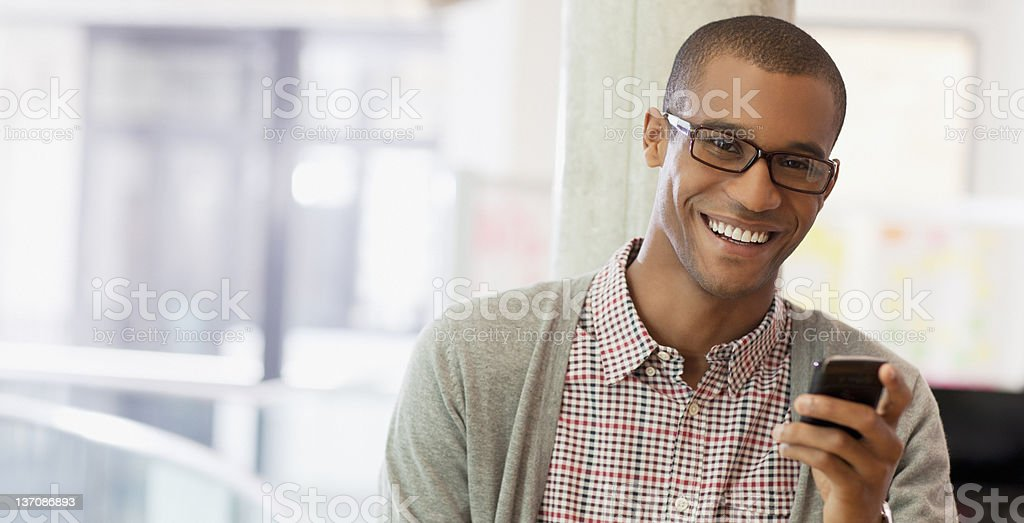 Portrait of smiling businessman with cell phone stock photo