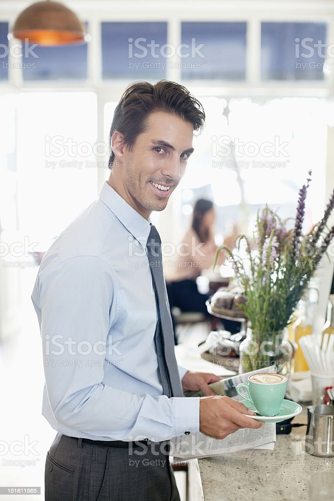 Portrait of smiling businessman with coffee and newspaper in cafe royalty-free stock photo