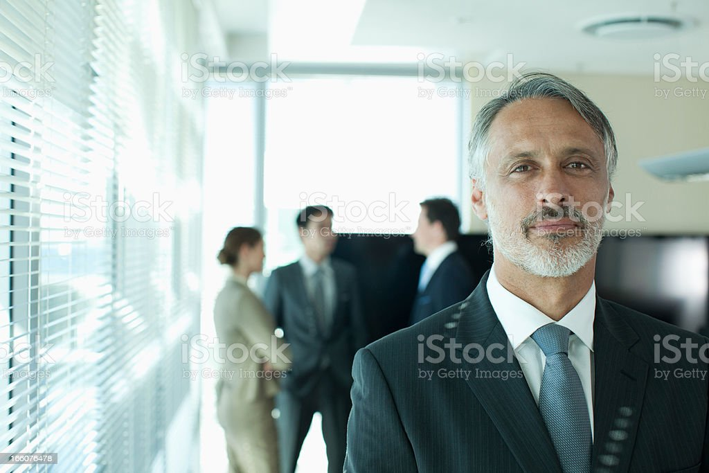 Portrait of smiling businessman with co-workers in background royalty-free stock photo