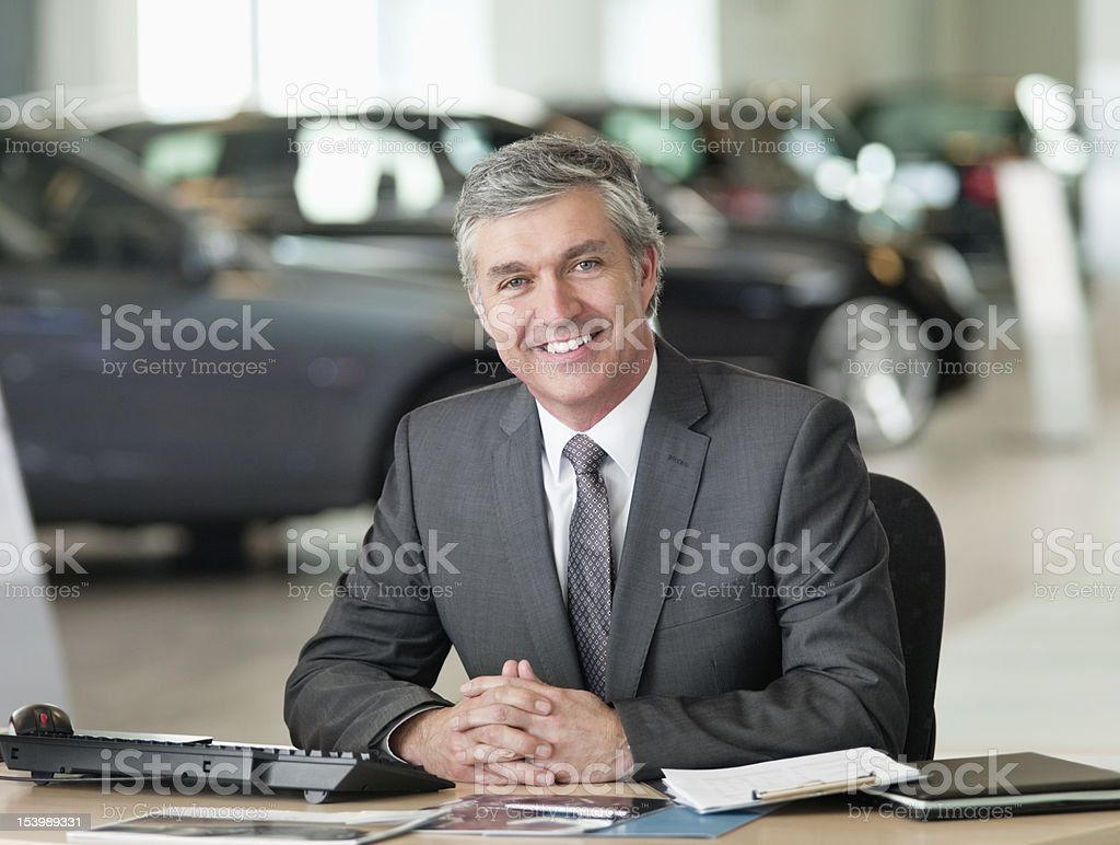 Portrait of smiling businessman with hands clasped at desk in car dealership showroom stock photo