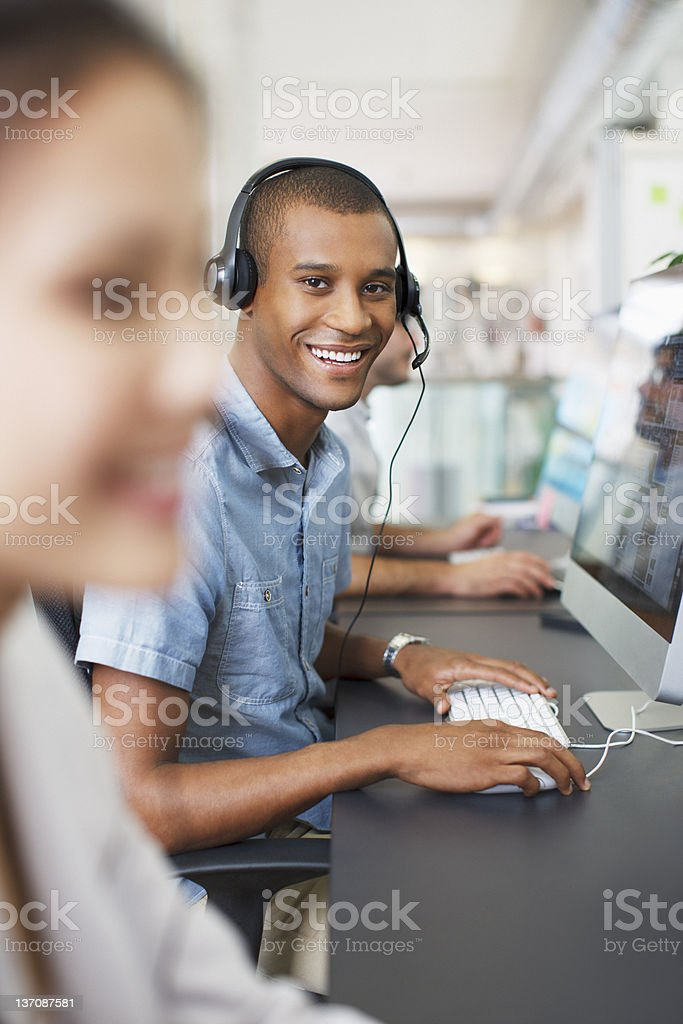 Portrait of smiling businessman with headset at computer in office stock photo