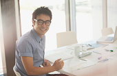 Portrait of smiling businessman working at conference room table