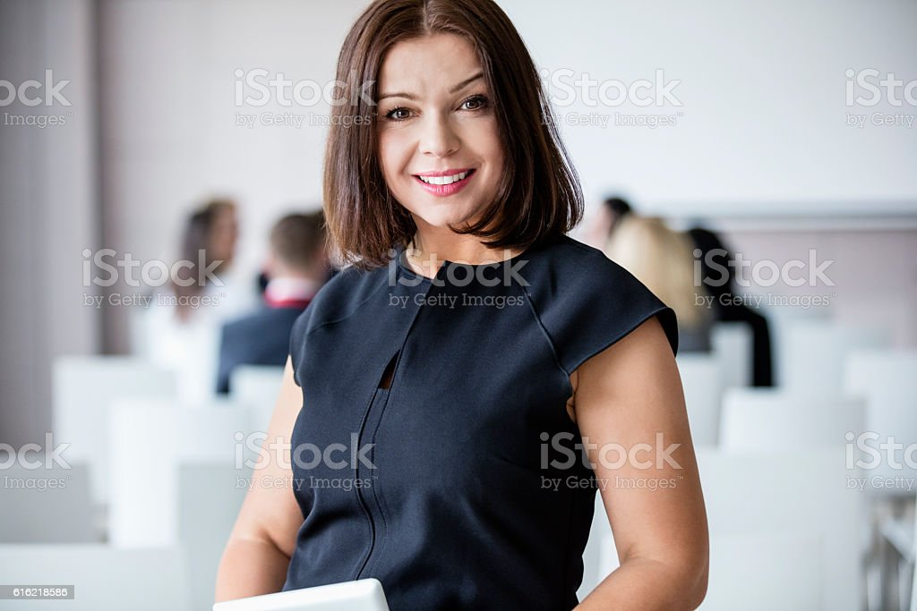 Portrait of smiling businesswoman standing in seminar hall stock photo