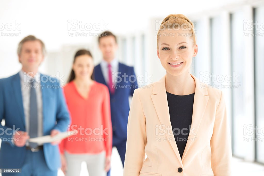 Portrait of smiling businesswoman with colleagues in background at office stock photo