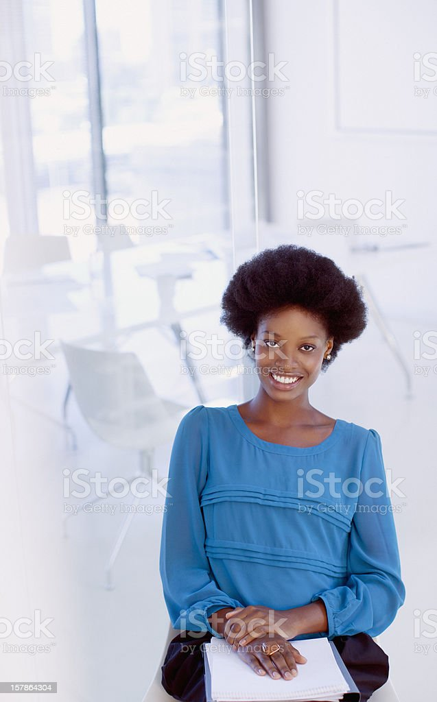 Portrait of smiling businesswoman with paperwork in office royalty-free stock photo